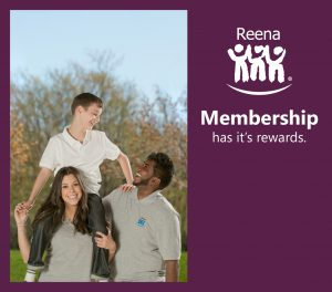Boy smiling on the shoulders of Reena staff members