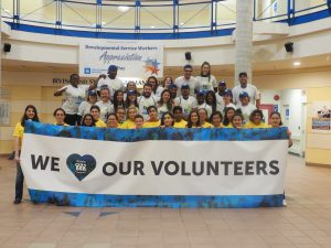 "A group shot of a bunch of young people holding up a sign that reads ""We love our volunteers"""